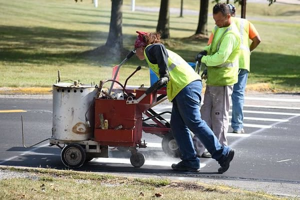 Employees using specialized road line painting equipment to paint lines on the road